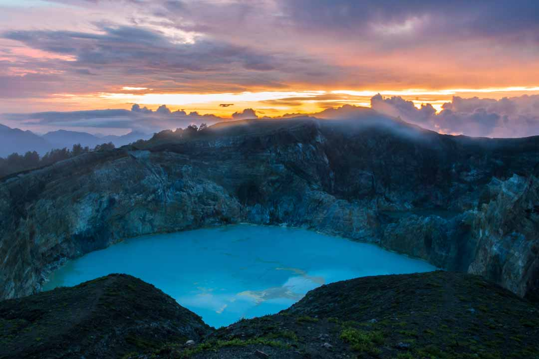 The Kelimutu volcanic crater. A turquoise coloured vast mineral lake is surrounded by the dramatic crater walls. The lake itself is near luminous in the red twilight.