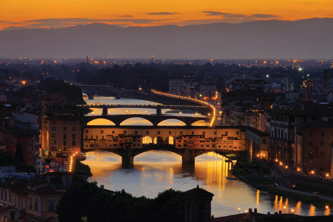 Florence by night. Illuminated street lamps light the bank of the river Alno. Three bridges are revealed by the reflections from the water. The closest bridge is covered in houses and has three archways allowing us to see through to the other side. In the background the city stretches into the distance.