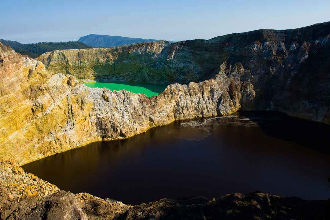 The Kelimutu volcanic crater. Two of the vast mineral lakes are surrounded by the dramatic crater walls. The first lake in the foreground appears black, the further lake is a shade of light green.