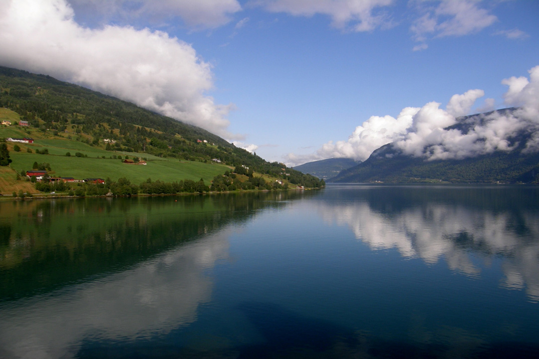 A tranquil fjord with green hills sloping down towards the waters edge. A pure blue sky overhead