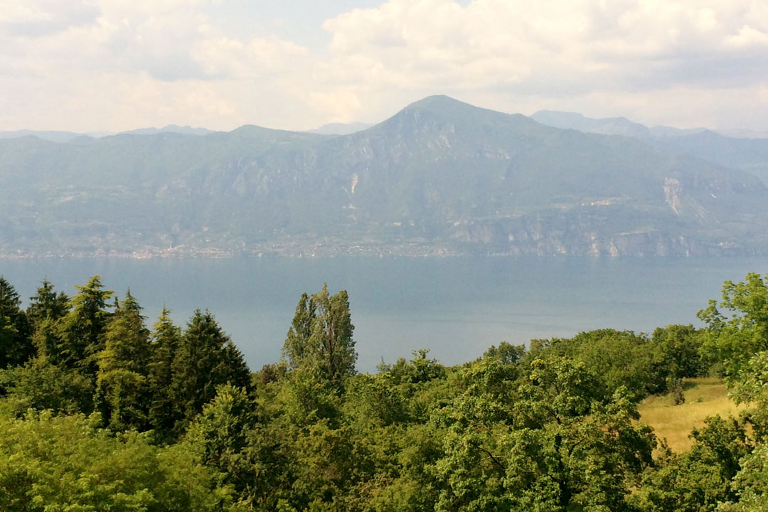 The rocky shores of Lake Garda. Bright green trees on the near side of the lake and ominous rocky mountains on the far shore of the Lake