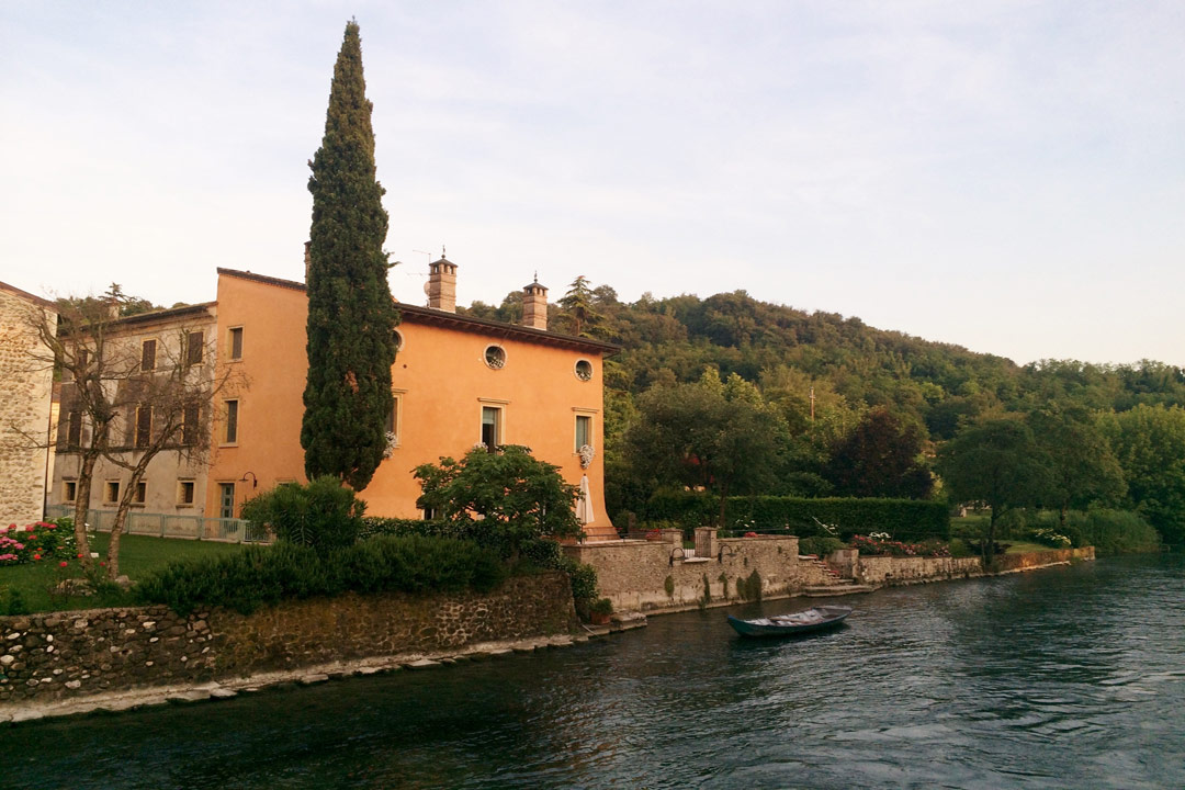 A typical Italian pastel villa on the shores of the lake. A small vessel is bobbing up and down. A forested hill is in the background behind the villa