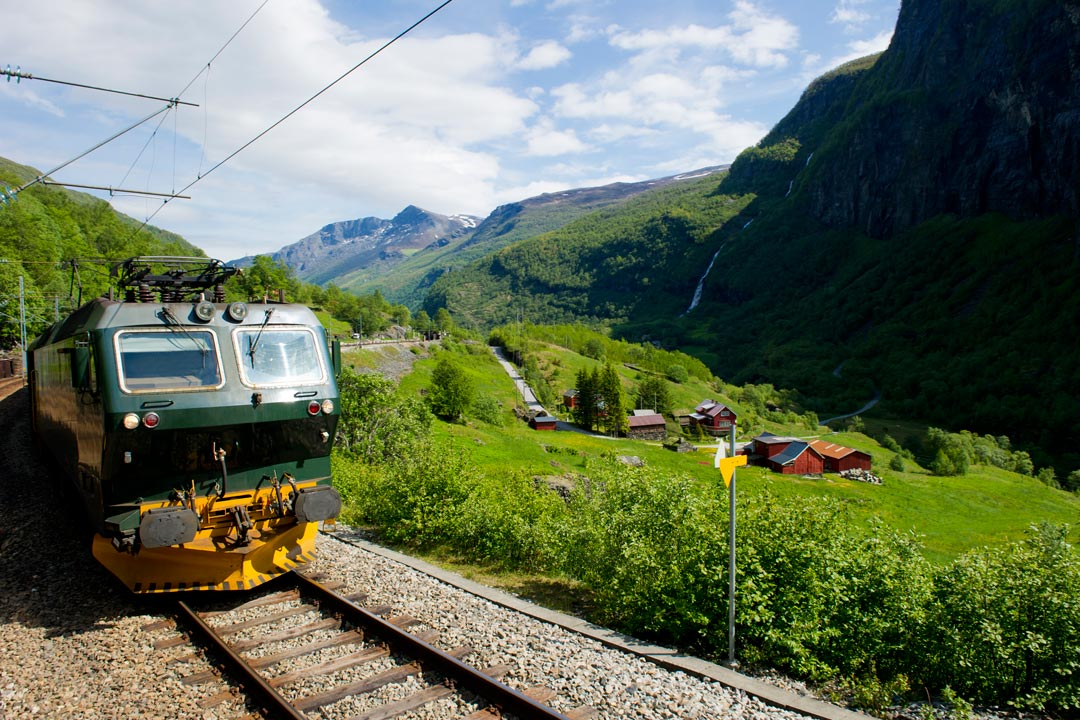 A train climbs through a beautiful valley. There are sheer cliffs in the foreground and background and lots of bright green grass and plants