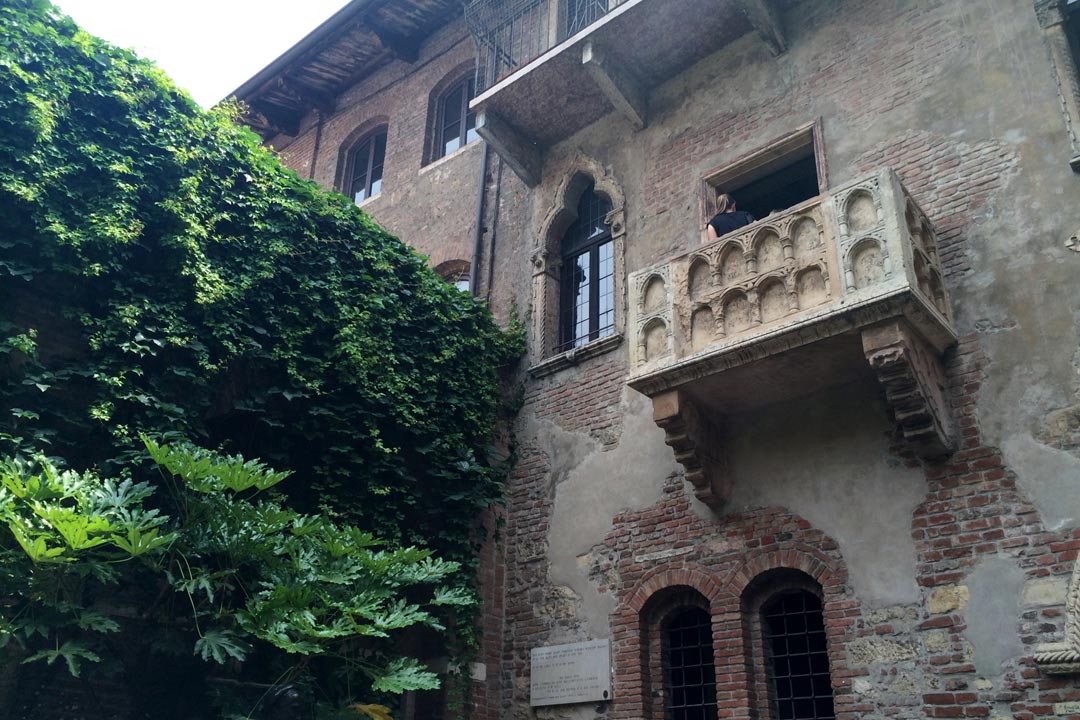 A balcony sticks out from an old stone building in Verona. Ivy is growing on the adjacent wall.