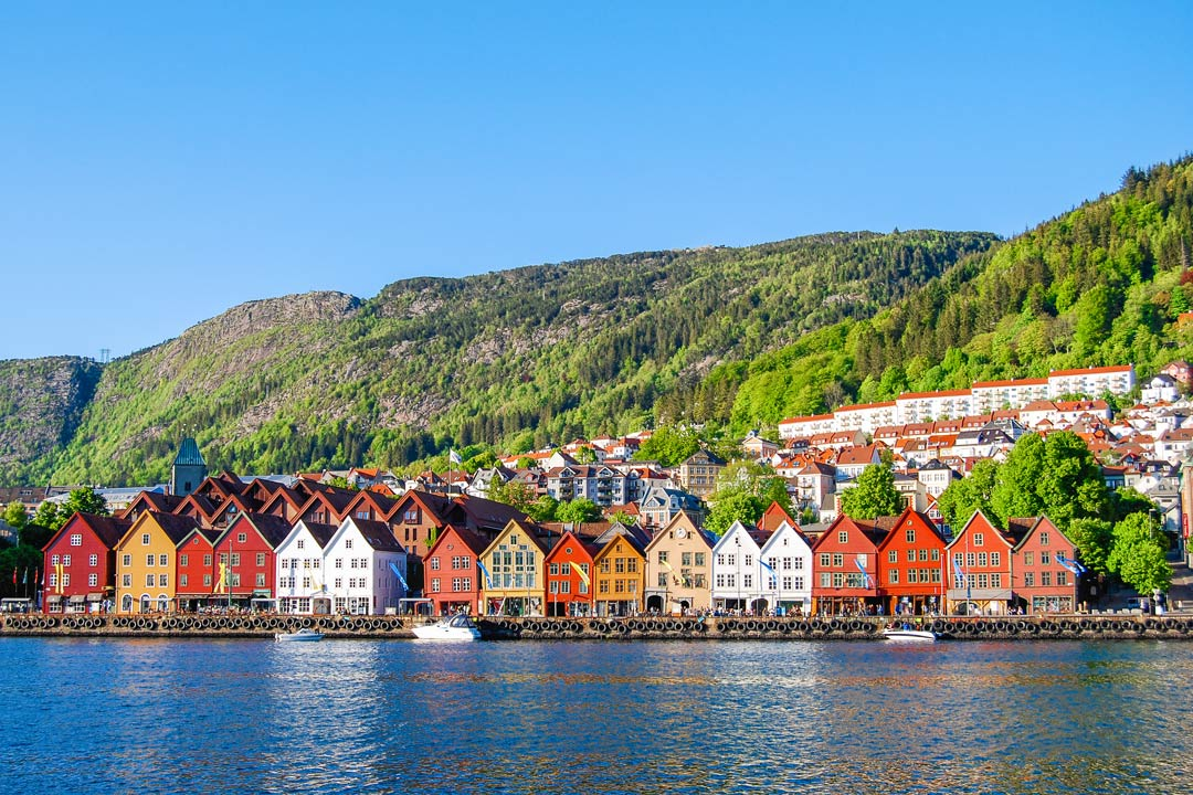 Multi-coloured houses with triangular roofs line the shore. Bright green trees cover the side of a steep hill behind the town.