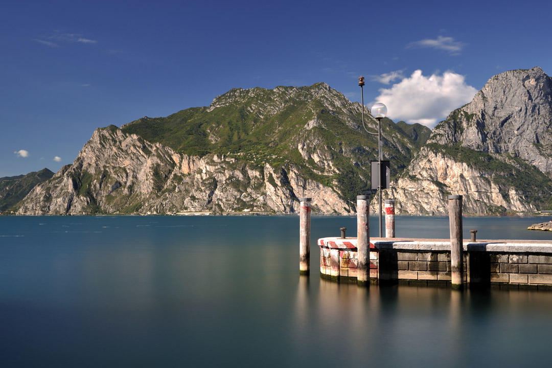 A jetty sticks out into the pure blue Lake. On the opposite shore there is dramatic cliff faces covered with green grass and grey rock