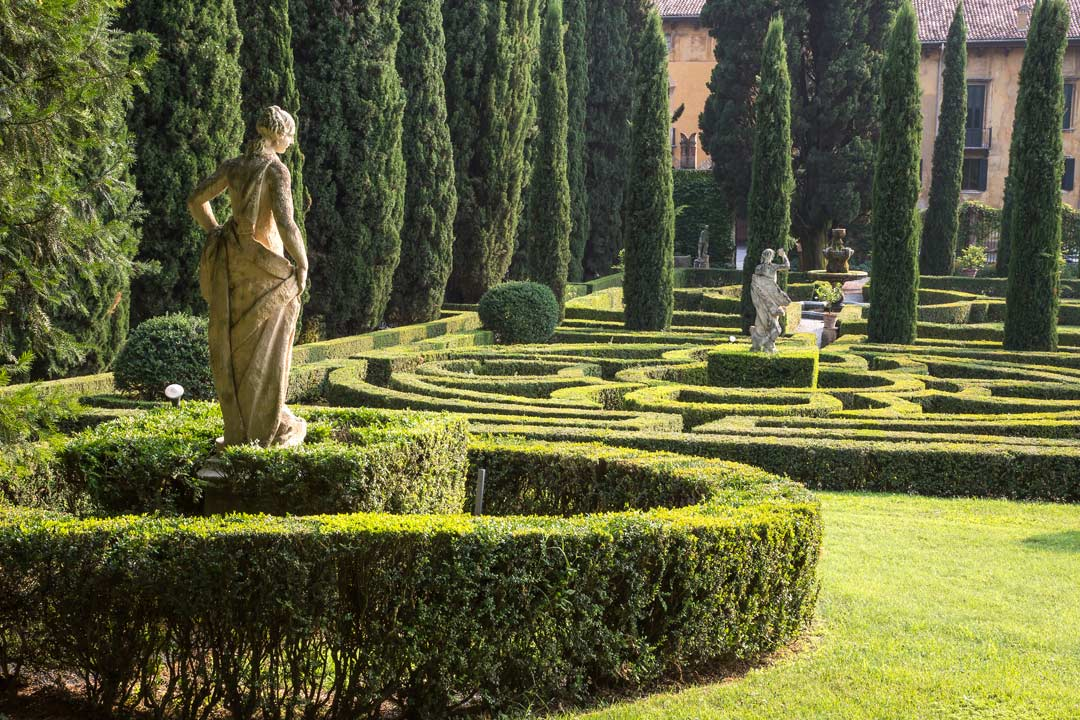 Ornamental gardens with marble figurines in the centre of spiralling hedge