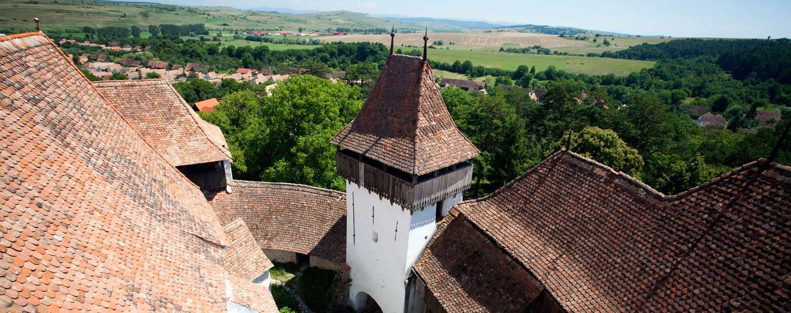 A Transylvanian Saxon Citadel showing a tall white tower and ramparts topped by steep roofs covered in circular red tiles