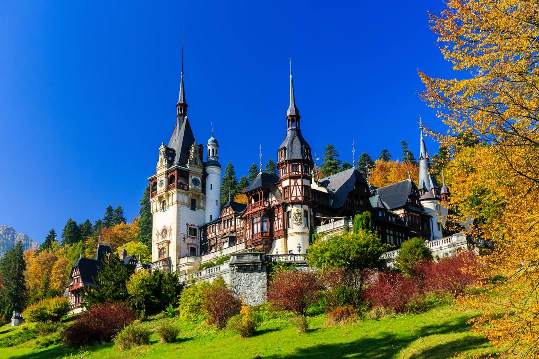 A residential castle sitting atop a hill decorated by steep spires and covered in a tudor-style wooden facade