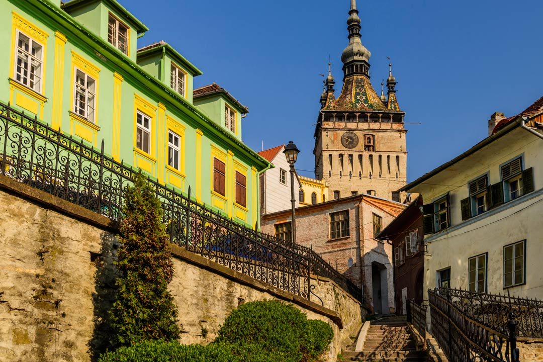 Steps leading up to a tall and wide tower with a typically orthodox coloured roof topped by an onion-shaped spire