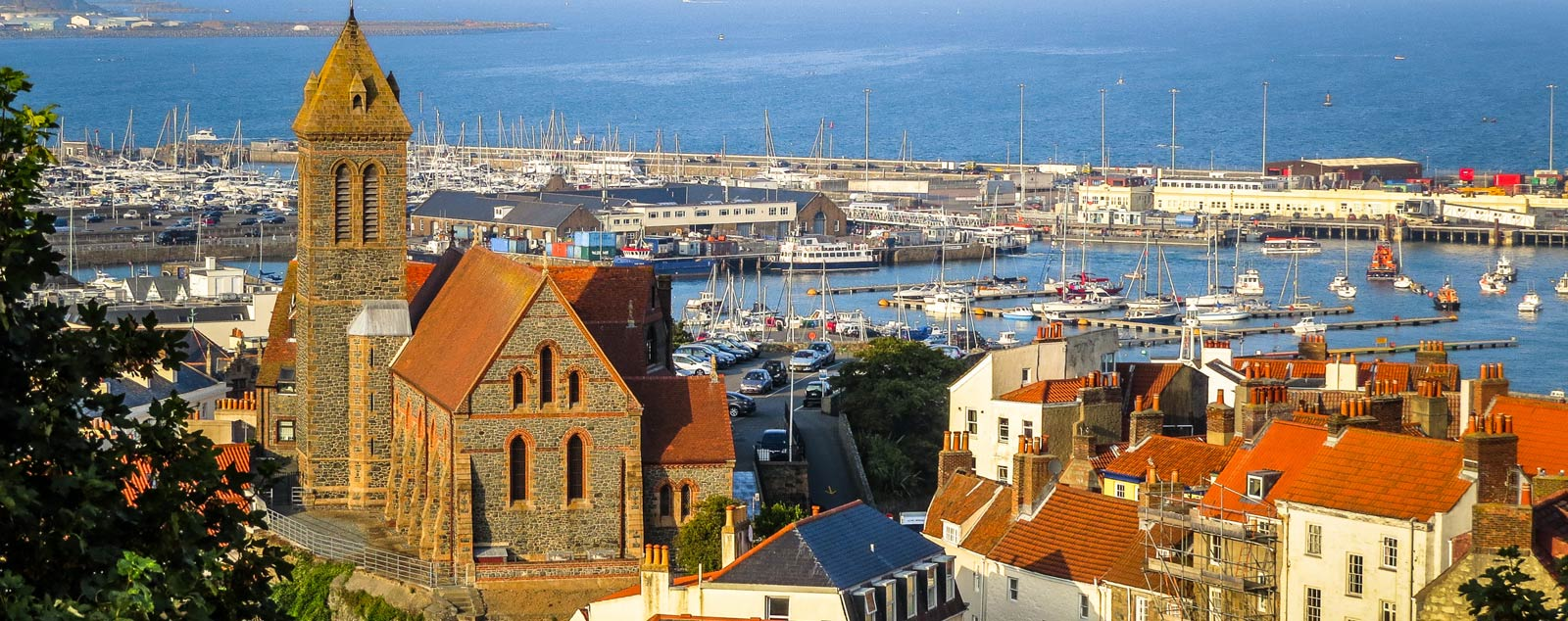 St Peter's Port harbour. A church sits at the top of the hill with houses leading down to the port filled with sailing ships