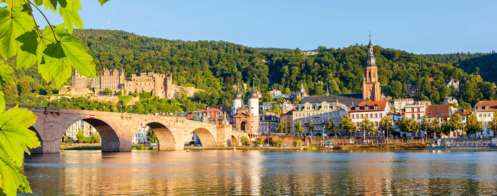 A stone bridge made of arches streches across a calm river to an old town overlooked by a castle and green forest
