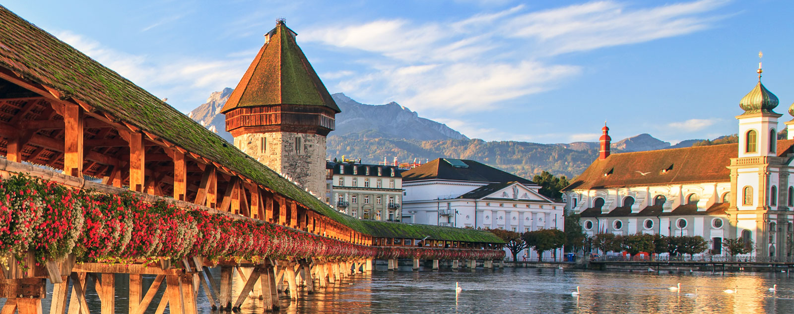 A medieval roofed bridge covered in flowers crosses a river leading to a tall stone tower in Lucerne