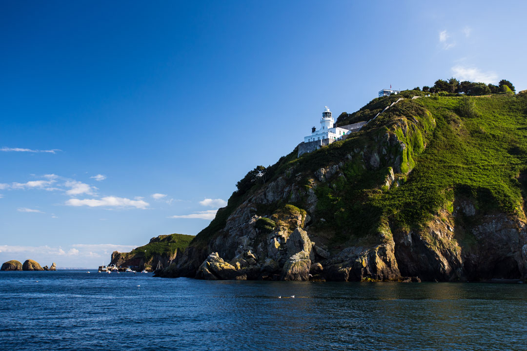 A lighthouse is perched on the edge of a steep cliff