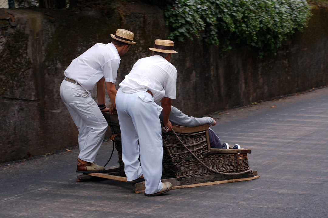 Two Madeiran men in white shirts and straw hats are pushing someone in a wicker sleigh