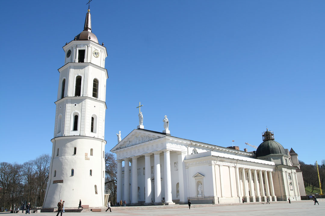 A classical style white church with a separate white bell tower next to it