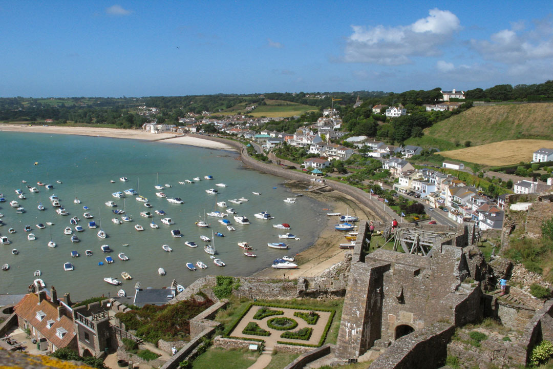 A view from stone ramparts with many boats moored next to a beach and the coastline lined with houses and green fields