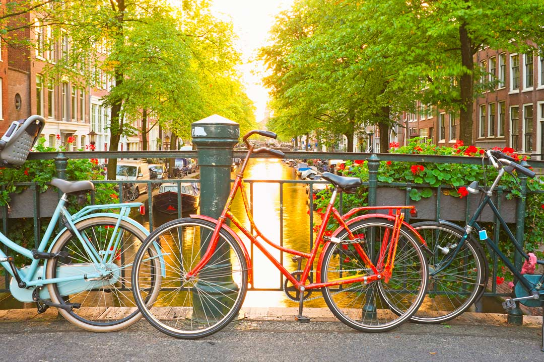 bicycles leaning against a bridge crossing a canal in Amsterdam