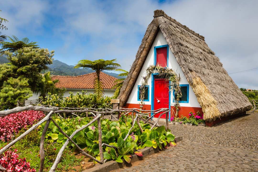A traditional Madeiran triangular house with a thatched roof