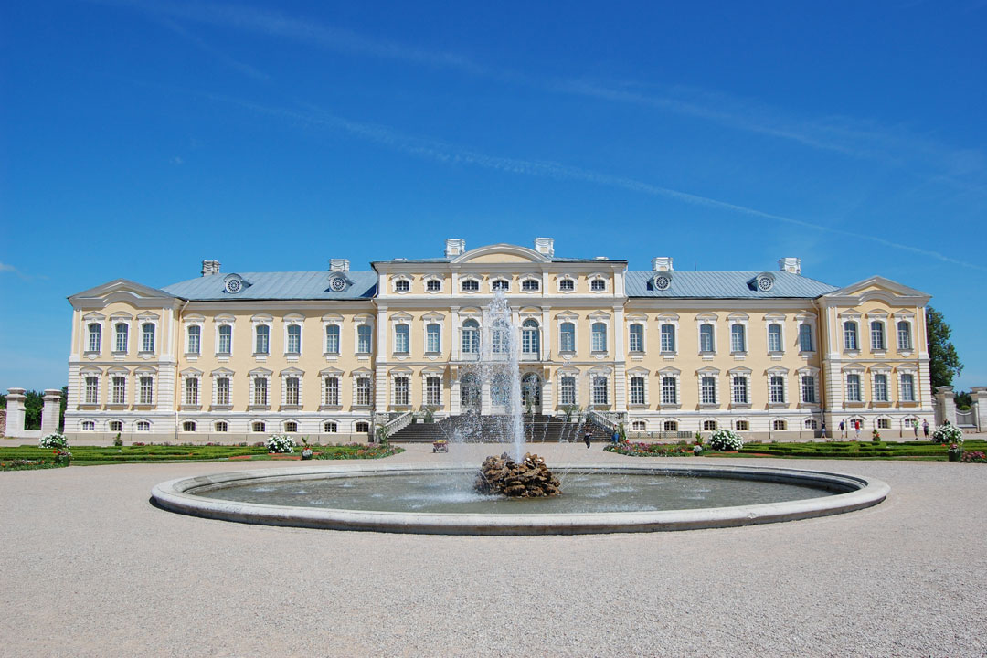 A white baroque palace facade with an ornate round fountain in front of it