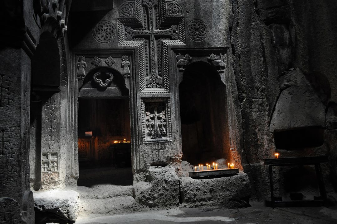 A crucifix is carved into the wall of an old stone church that is lit by candlelight
