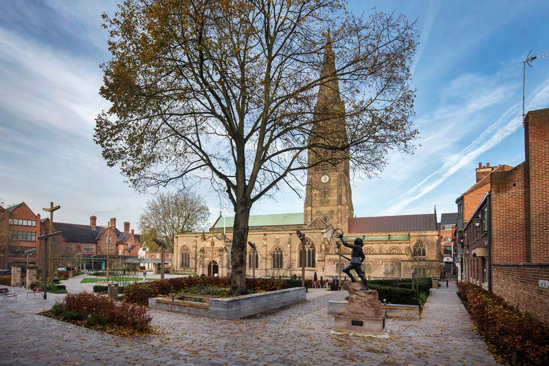 A courtyard with Leicester cathedral, green bushes and benches