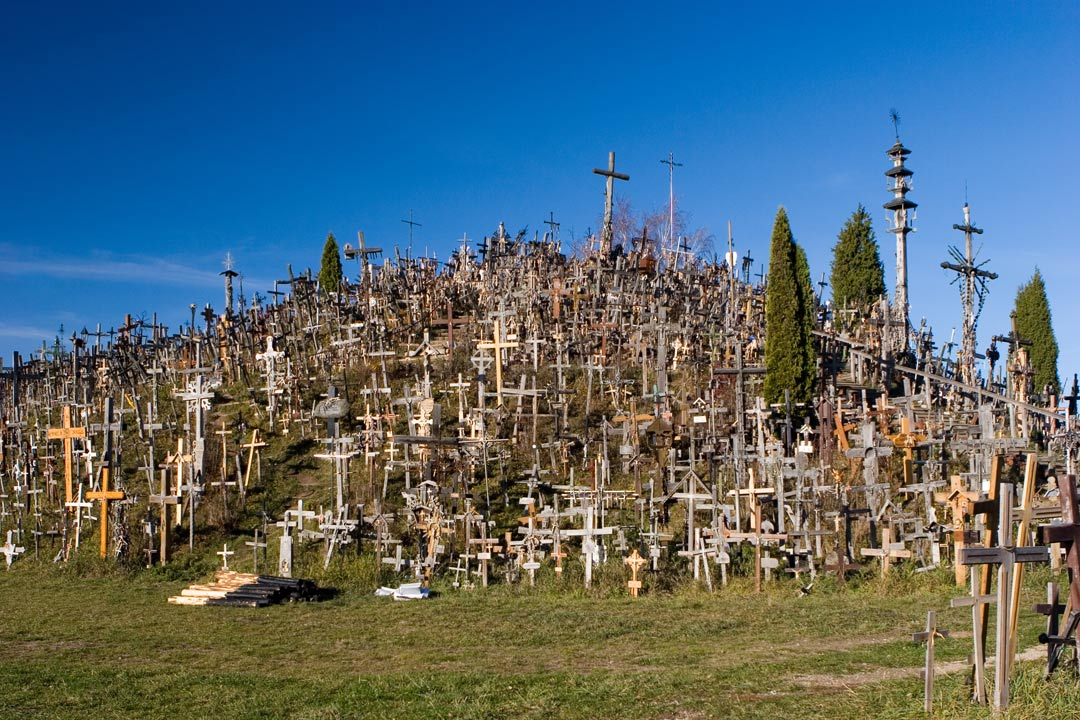 A green hill completely covered by hundreds of crosses and crucifixes