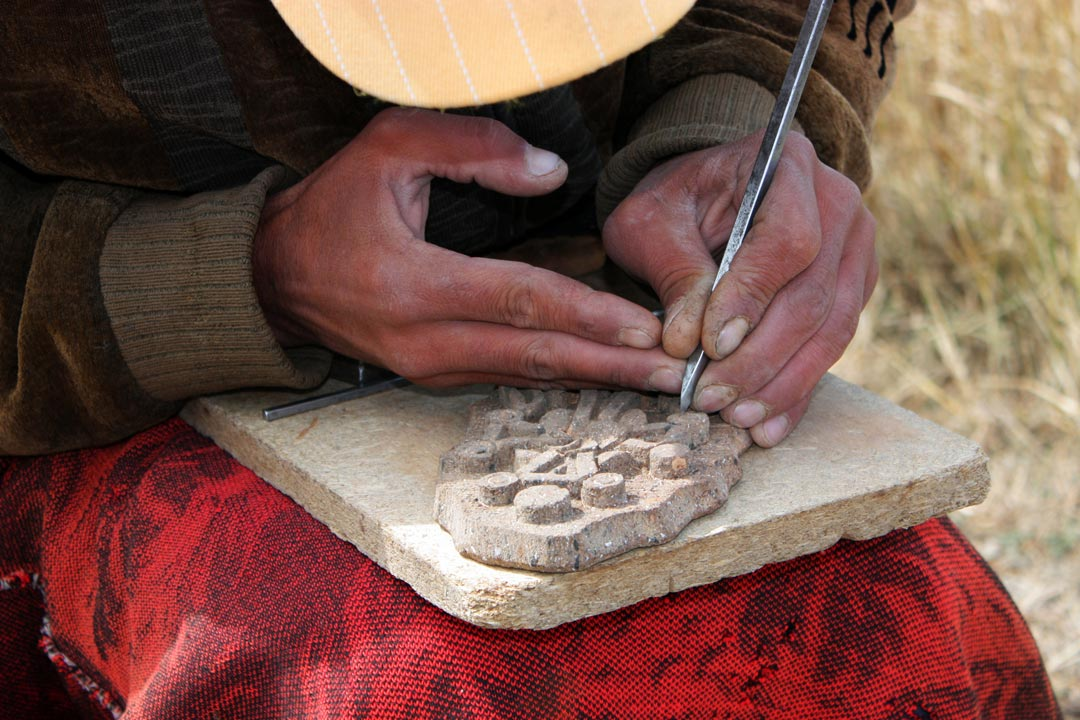 A local is crafting a model made of stone