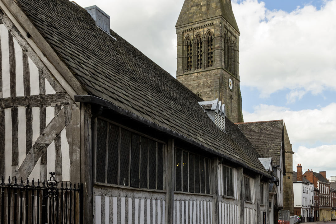 A wattle and daub building in the Tudor style with Leicester cathedral spire in the background