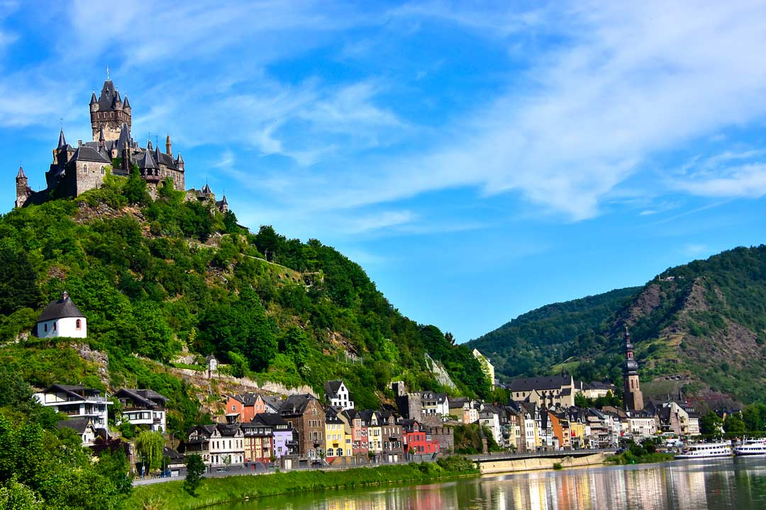An old town on the Rhine overlooked by an imposing black roofed fortress on a steep hill