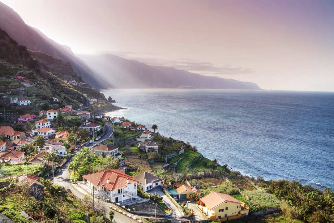 Madeira's dramatic steep coastline white houses cling to the coastline