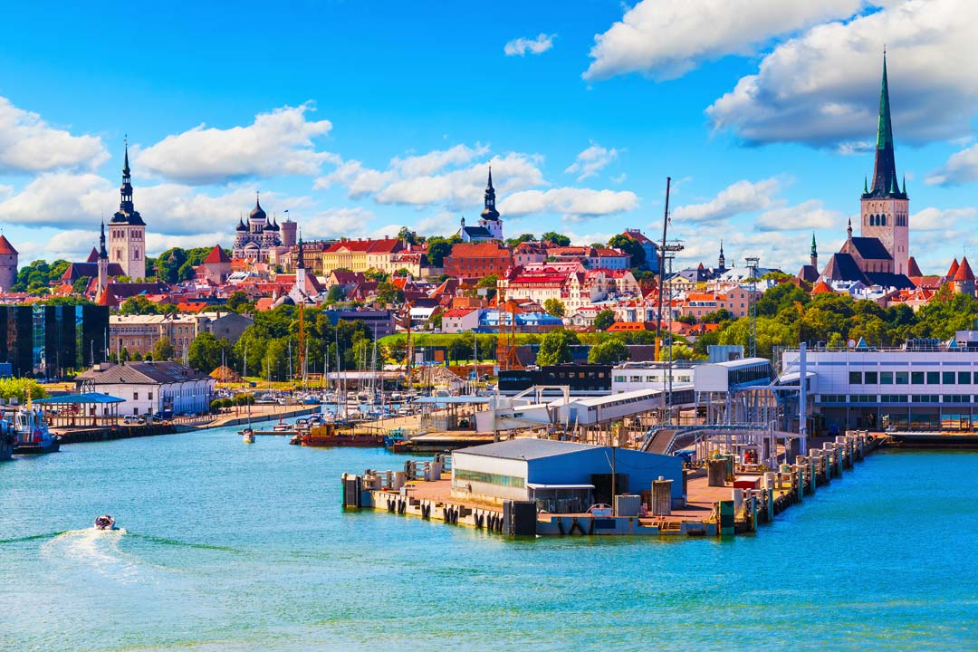 The Baltic Sea leading to a town of red terracotta roofed townhouses and black domes churches