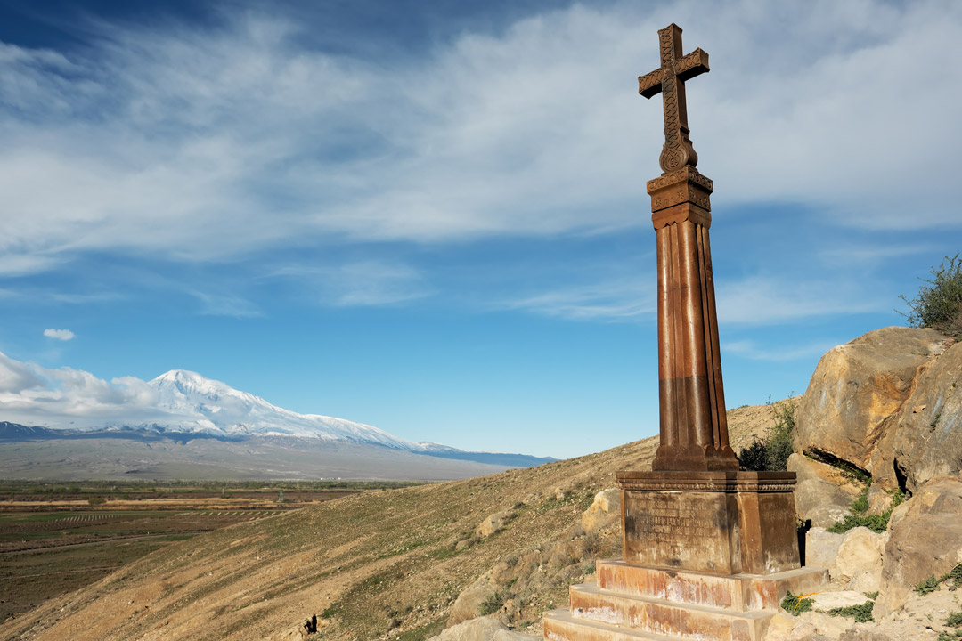 A statue of the crucifix stands alone with vast plains and then a snow topped mountain in the distance