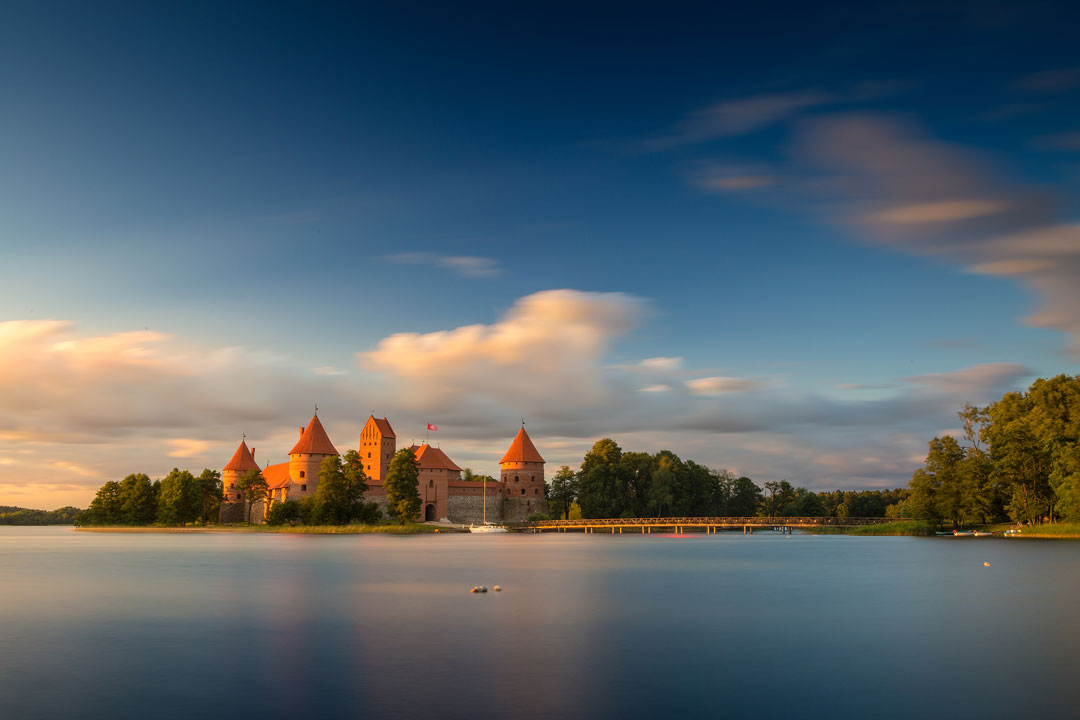 A calm smooth blue lake with a medieval fortress in the background
