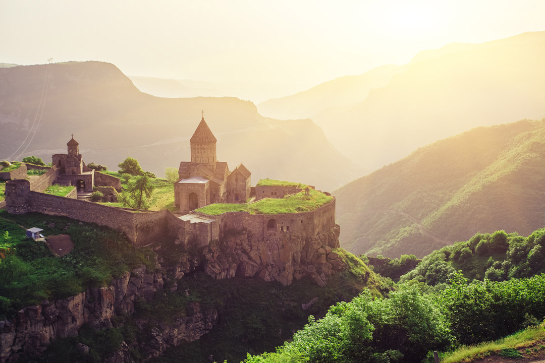 A monastery complex sits on a cliff edge with dramatic and steep mountains in the background