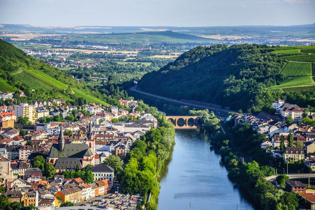 The blue Rhine River sandwiched between a green valley of vineyards and small villages