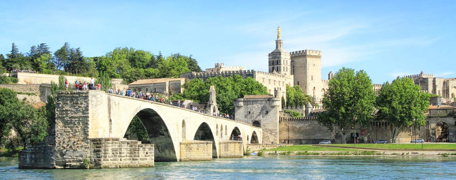 Avignon's famed bridge sticks out half way into the river. The papal place and city walls are towering overhead in the background