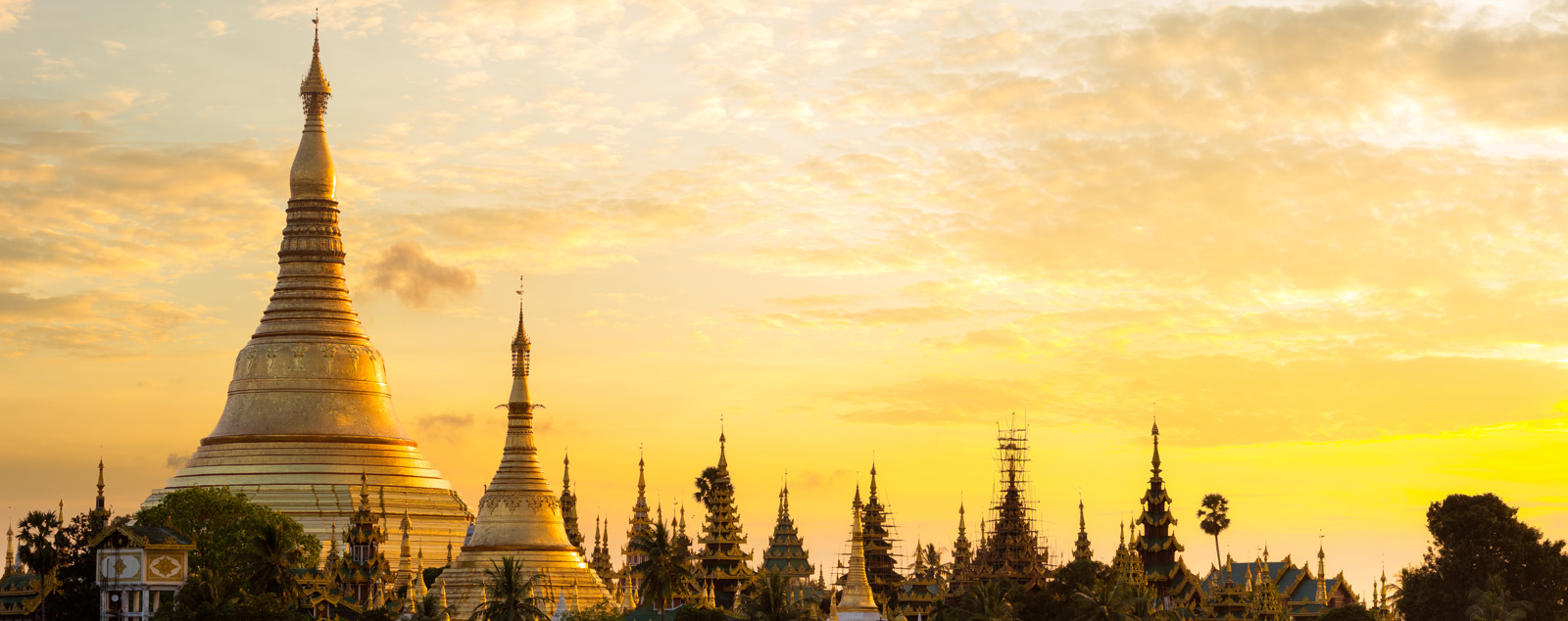 A tall golden pagoda spire reaching into the sky with a yellow sunset brightly reflecting off it