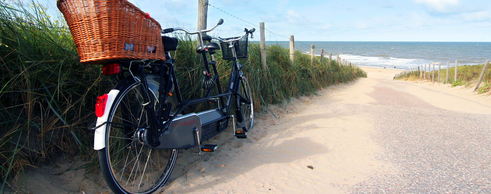 A tandem bike rests against the verge of a sandy path that leads down to the sea