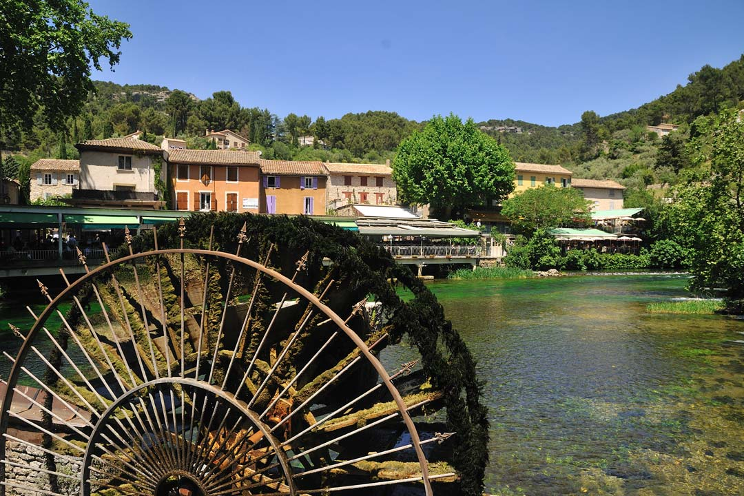 A water wheel is in the foreground with a typical french village built on the banks of the river