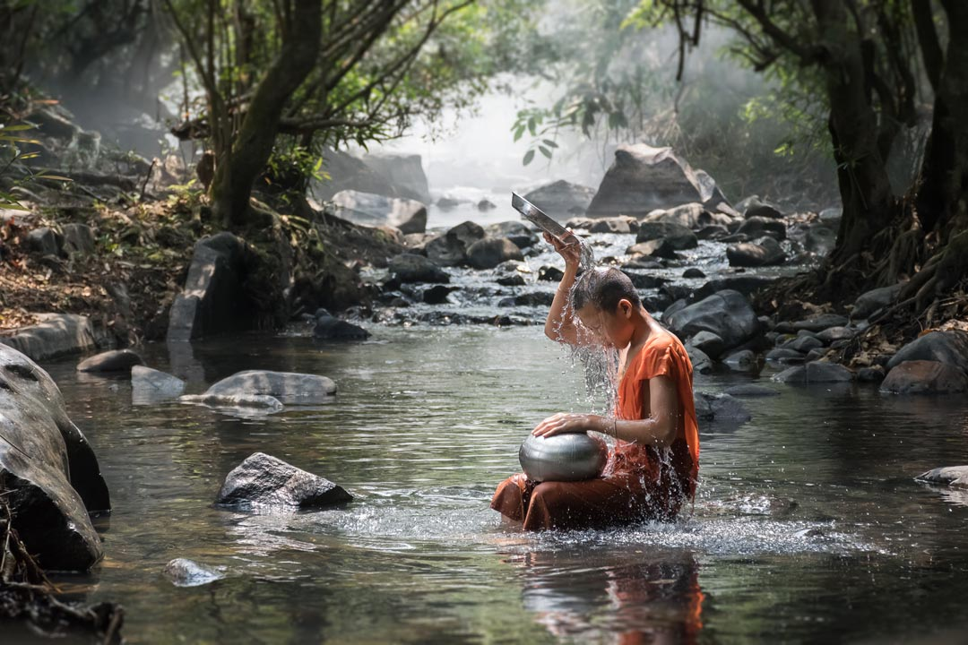 A child monk wearing traditional robes sits in a peaceful river pouring water on his head from a silver dish