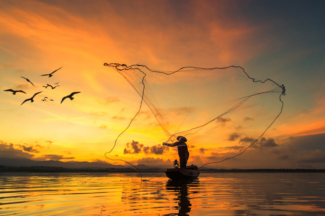 A fisherman standing on a small fishing boat throwing a huge net into the water at sunset