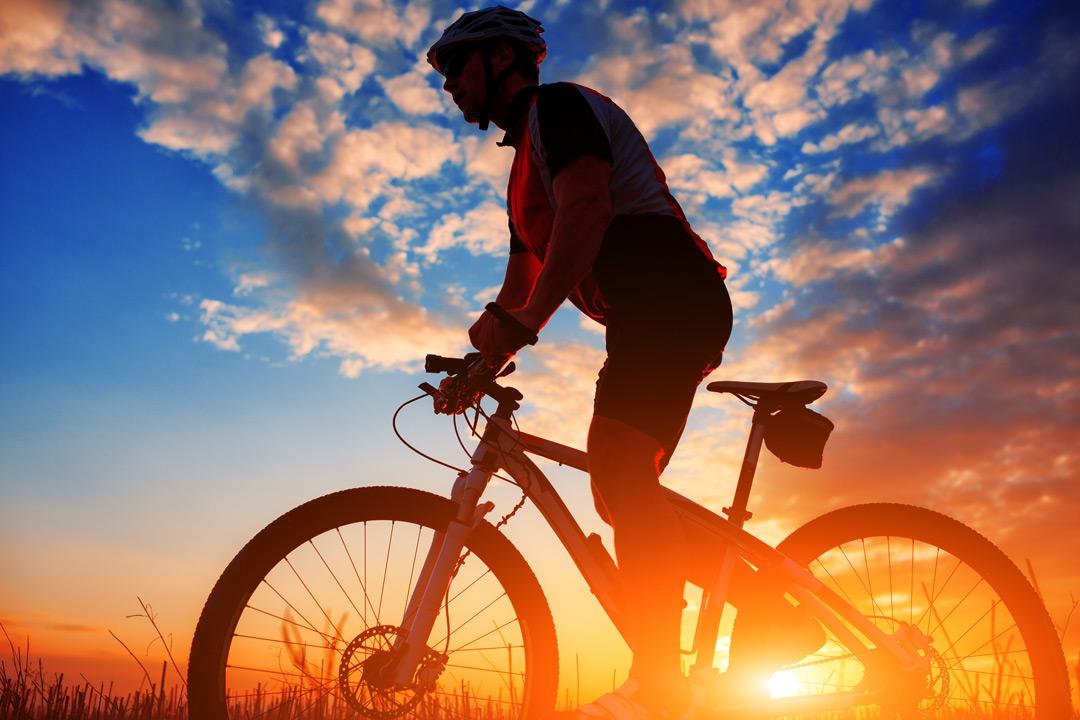 A man rides a bike through a field with a bright sunset behind him
