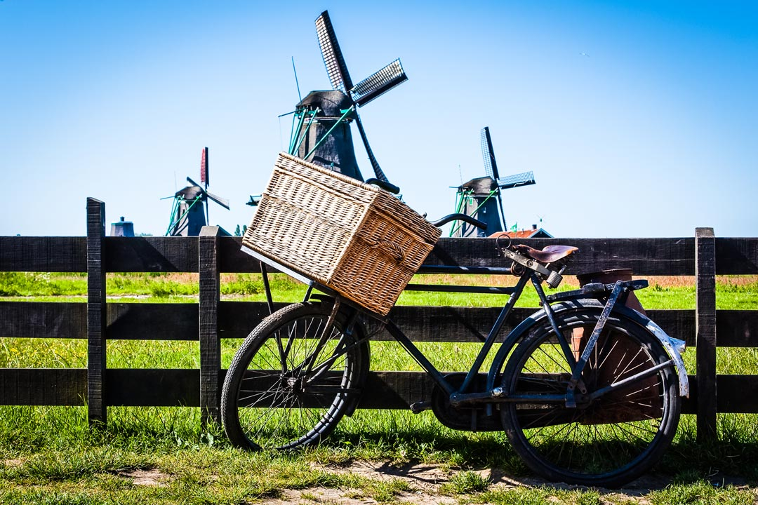A bike with traditional wicker basket rests against a fence with four windmills in the background