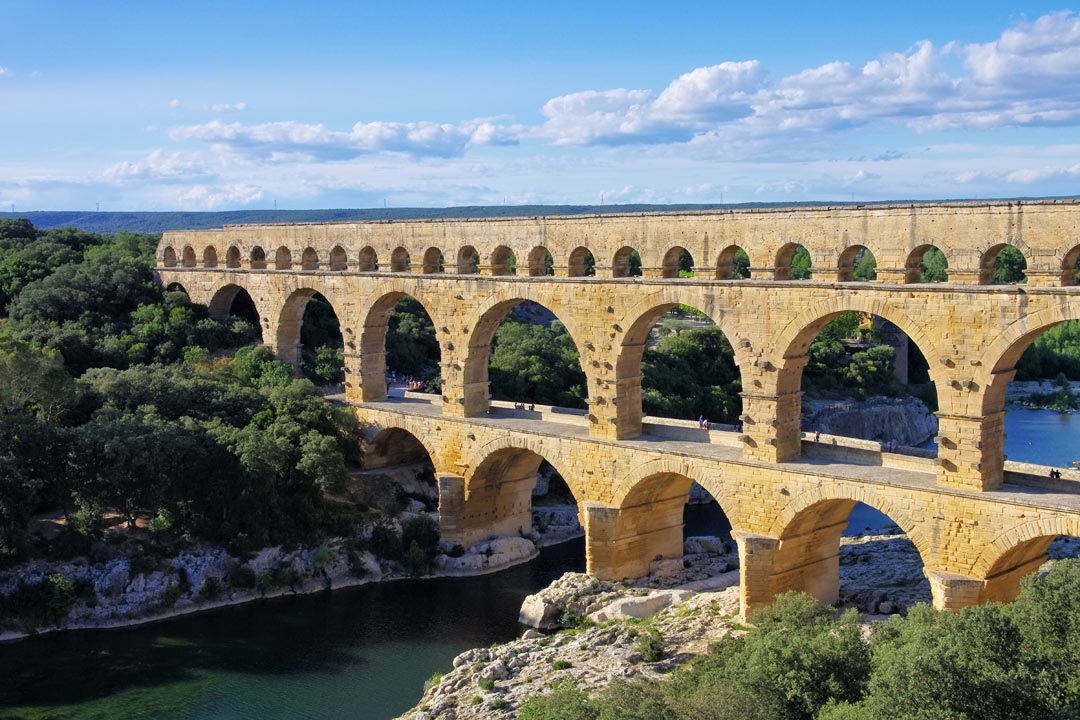 A huge double tiered stone Roman aqueduct that crosses the river