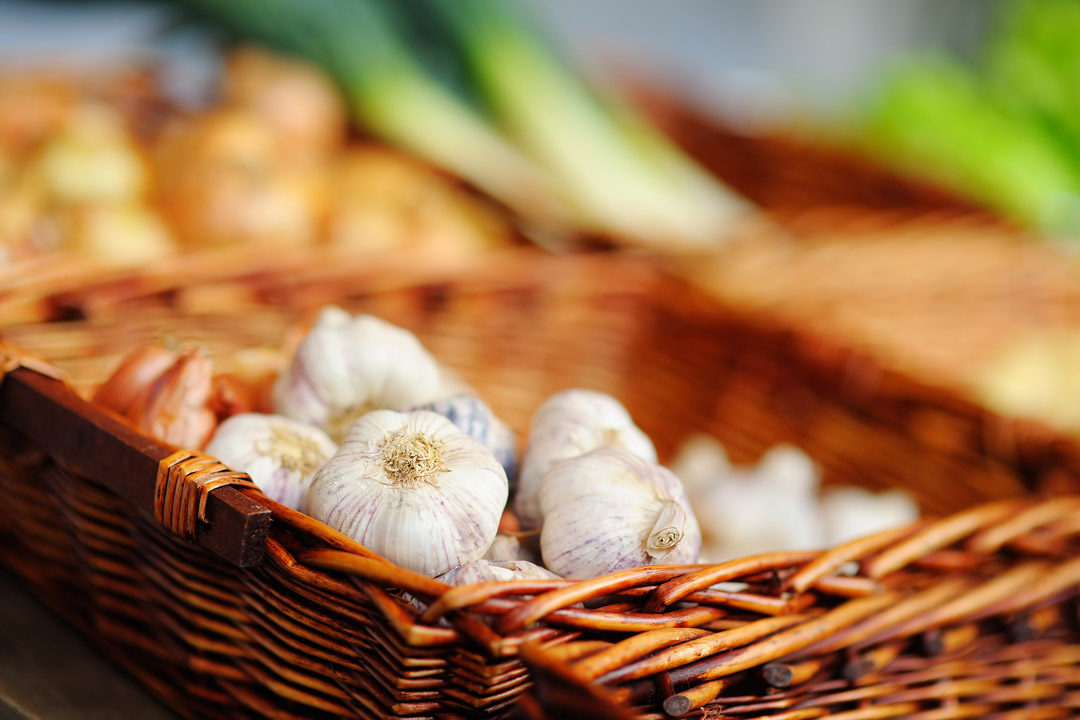A wicker basket full of garlic cloves