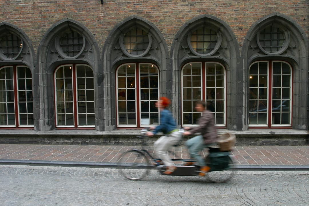 A tandem bike quickly cycling by several arched window