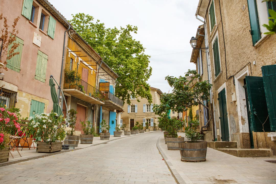 A typical street in a French village with potted trees and shuttered stone houses