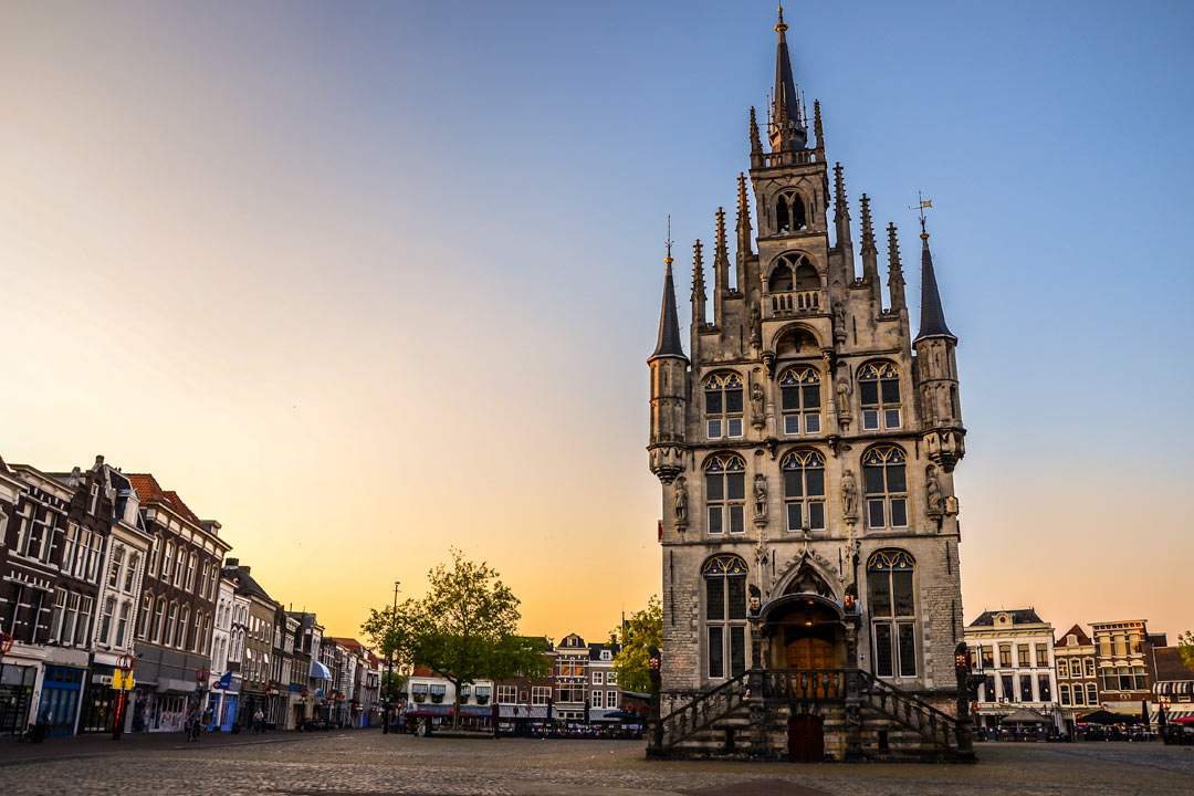 A small but ornate building with numerous spires sits in the middle of a typically Dutch town square