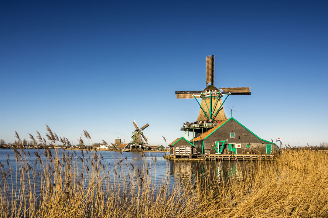 A floating windmill and farmhouse sit on the banks of a river, another can be seen in the background